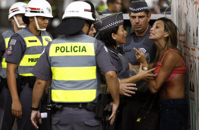 A demonstrator argues with policewomen after she turned up her shirt and was taken out from a protest to demand the resignation of Brazilian President Dilma Rousseff, on March 13, 2016 in Paulista Avenue in Sao Paulo. Protesters, many draped in the Brazilian national flag, poured into the streets of Brasilia and Rio de Janeiro on Sunday at the start of mass demonstrations seeking to bring down President Dilma Rousseff. Authorities in Sao Paulo, Brazil's biggest city and an opposition stronghold, said they were bracing for a million protesters. (Photo by Miguel Schincariol/AFP Photo)