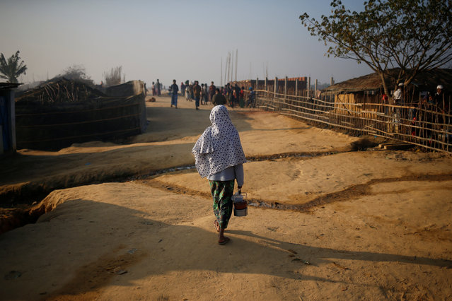 A Rohingya refugee walks on with a tiffin carrier in the morning at Kutupalang Unregistered Refugee Camp, in Cox's Bazar, Bangladesh, February 4, 2017. (Photo by Mohammad Ponir Hossain/Reuters)