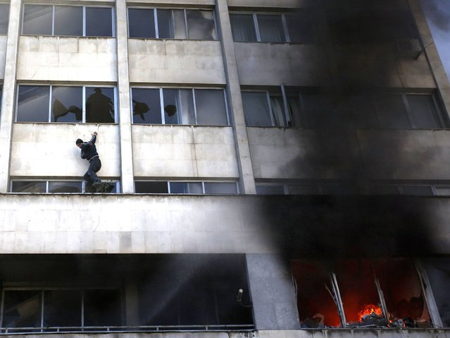 A man climbs out of a window as smoke rises from a blaze at a government building in Tuzla, February 7, 2014. (Photo by Dado Ruvic/Reuters)