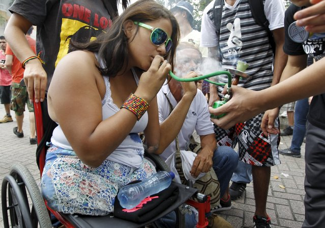 A woman smokes marijuana during a demonstration in support of the legalization of marijuana in Medellin, May 2, 2015. (Photo by Fredy Builes/Reuters)