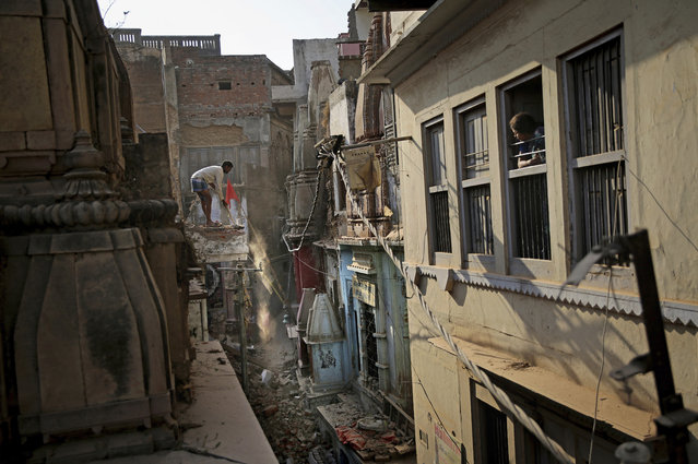 In this March 19, 2019 photo, a woman watches from her window as a worker demolishes a house at the site of a proposed grand promenade connecting the sacred Ganges river with a centuries-old temple dedicated to Lord Shiva, in Varanasi, India. The $115 million promenade is just one of a number of India Prime Minister Narendra Modi's religious glamor projects, aimed squarely at pleasing his Hindu nationalist base ahead of elections that start this month. (Photo by Altaf Qadri/AP Photo)