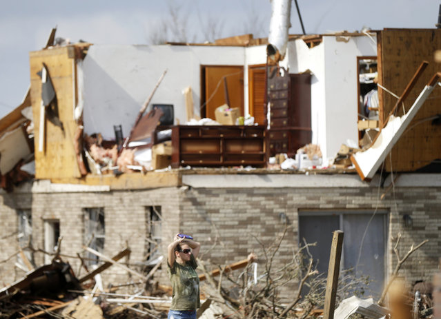 A woman walks past a destroyed home in the aftermath of Tuesday's tornado that tore through the New Orleans East section of New Orleans, Wednesday, February 8, 2017. (Photo by Gerald Herbert/AP Photo)