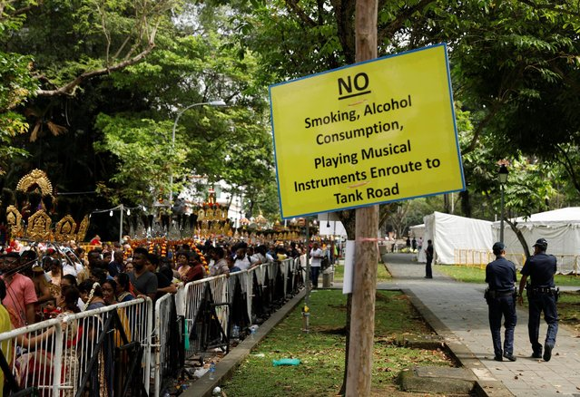 A sign hangs outside a temple as devotees line up in their kavadis during the Hindu festival of Thaipusam in Singapore February 9, 2017. (Photo by Edgar Su/Reuters)