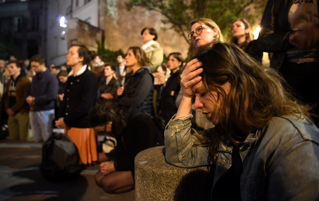People kneel on the pavement as they pray outside watching flames engulf Notre-Dame Cathedral in Paris on April 15, 2019. (Photo by Eric Feferberg/AFP Photo)
