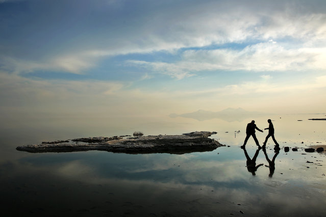 In this Saturday, February 15, 2014 photo, two men walk toward salt-covered rocks that were once deep underwater at Lake Oroumieh, in northwestern Iran. Oroumieh, one of the biggest saltwater lakes on Earth, has shrunk more than 80 percent to 1,000 square kilometers (nearly 400 square miles) in the past decade, mainly because of climate change, expanded irrigation for surrounding farms and the damming of rivers that feed the body of water, experts say. (Photo by Ebrahim Noroozi/AP Photo)