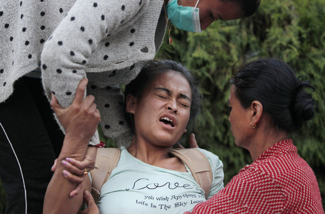 A Nepalese victim of Tuesday's earthquake tries to sit up with the help of family members at Teaching Hospital in Kathmandu, Nepal, Tuesday, May 12, 2015. A major earthquake has hit Nepal near the Chinese border between the capital of Kathmandu and Mount Everest less than three weeks after the country was devastated by a quake. (Photo by Niranjan Shrestha/AP Photo)