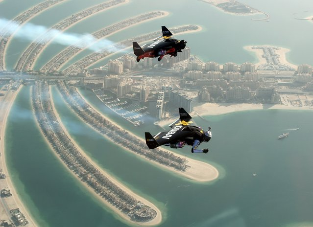 An aerial view taken from a sea plane shows Swiss pilot and original Jetman Yves Rossy (front) and Vince Reffett flying over Dubai's Palm Island, United Arab Emirates May 12, 2015. (Photo by Lara Sukhtian/Reuters)