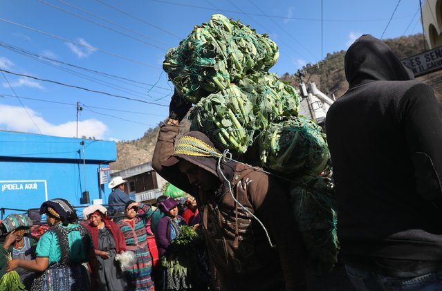 A porter carries a load through a vegetable market on February 11, 2017 in Almolonga, Guatemala. (Photo by John Moore/Getty Images)