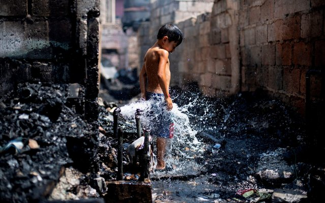 A boy enjoys water coming from a busted pipe that was damaged after a fire razed a slum area in Manila on April 20, 2019. Hundreds of families were left homeless after the fire, according to officials. (Photo by Noel Celis/AFP Photo)