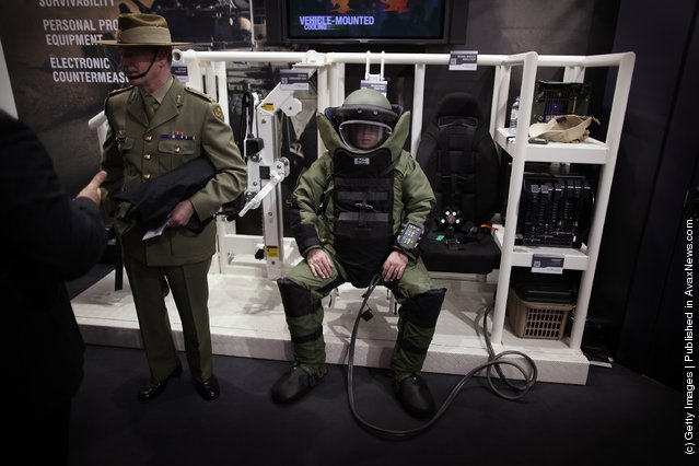 A soldier sits in an air cooled bomb disposal uniform at the Defence and Security Exhibition