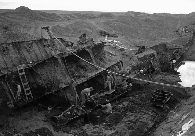 On the island of Iwo Jima, Japanese work crews cut up the wreckage of a naval vessel which was almost completely covered along the sandy beach on February 21, 1954. After a nine-year absence, the Japanese are back on the island of Iwo Jima, but as salvage workers. (Photo by AP Photo via The Atlantic)
