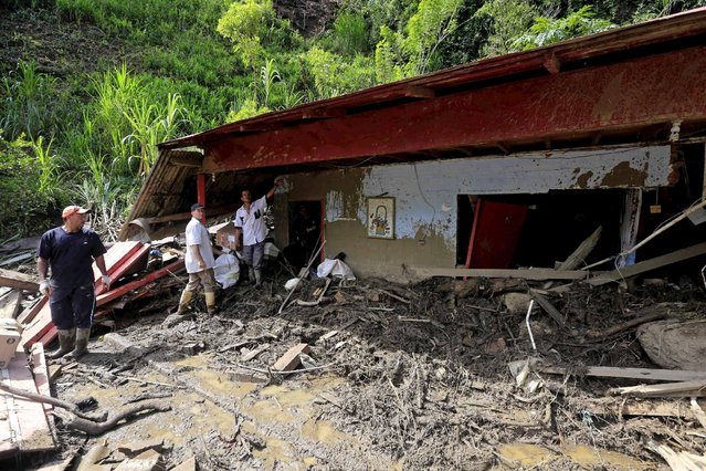 Residents remove debris from their damaged house, after a landslide sent mud and water crashing onto homes close to the municipality of Salgar in Antioquia department, Colombia May 19, 2015. (Photo by Jose Miguel Gomez/Reuters)