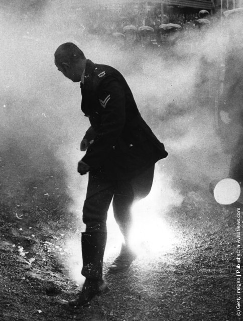 1971: A policeman loses his hat as he runs from a smoke bomb during rioting by anti-apartheid demonstrators at the Melbourne Olympic Park, Australia, during a match between the South African Springboks Rugby team and Victoria