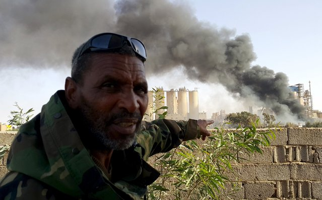 A member of military forces loyal to Libya's eastern government points to a fire near the Libyan cement factory during clashes with the Shura Council of Libyan Revolutionaries, an alliance of former anti-Gaddafi rebels who have joined forces with Islamist group Ansar al-Sharia, in Benghazi, Libya April 15, 2016. (Photo by Reuters/Stringer)
