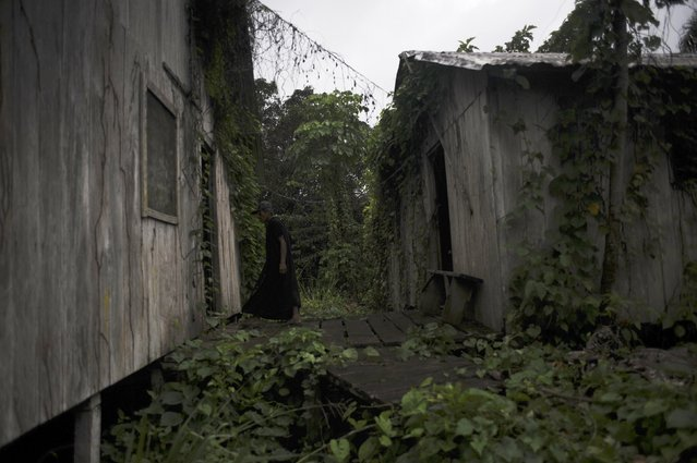 Ashaninka Indian, cacique (chief) Txate, walks between buildings of the former government base called the Envira Front of Ethno-environmental Protection along the Envira river in Brazil's northwestern Acre state, March 14, 2014. (Photo by Lunae Parracho/Reuters)