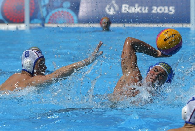 Bohdan Dzyadyk of Ukraine, right, fights for the ball with Maxim Gmyrya of Russia during the water polo competition at the 2015 European Games in Baku, Azerbaijan, Saturday, June 13, 2015. (AP Photo/Dmitry Lovetsky)
