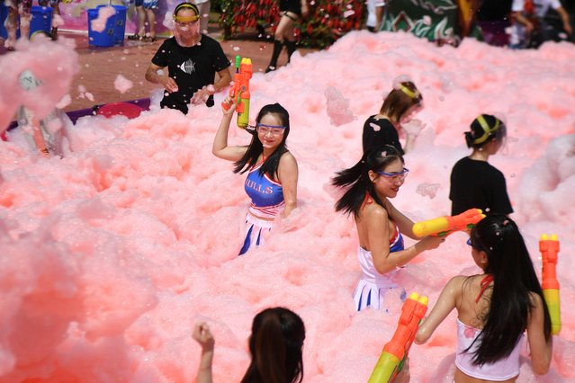 People hold water guns as they play inside a pool filled with foam bubbles mixed with chili liquid during an event on a hot day in Ningxiang, Hunan province, China on July 1, 2019. (Photo by Reuters/China Stringer Network)