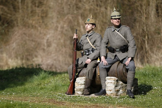Members of a German World War I historical association sit on the remains of a French long-range cannon at the wiped-out village of Bezonvaux. (Photo by Charles Platiau/Reuters)