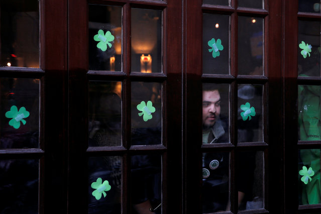 A man peers out from a bar on Saint Patrick's day in Manhattan, New York, U.S., March 17, 2017. (Photo by Andrew Kelly/Reuters)