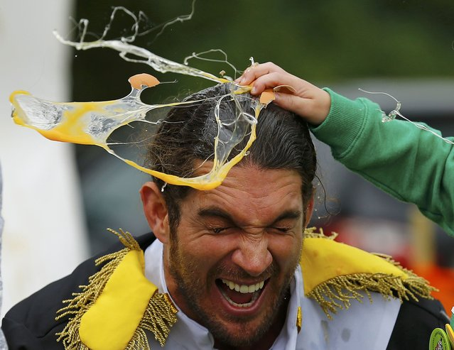 A man has an egg smashed on his head to raise money for charity during the World Egg Throwing Championships and Vintage Day in Swaton, Britain June 28, 2015. (Photo by Darren Staples/Reuters)