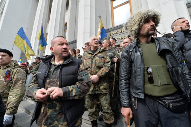 """Maidan self-defence activists guard the Ukrainian Parliament in Kiev during a session, on April 15, 2014, as protesters outside the building demand authorities to take actions against separatism on the eastern part of the country. Russian Foreign Minister Sergei Lavrov on Tuesday warned Kiev against using force to quell pro-Moscow separatists in eastern Ukraine, saying the """"criminal"""" act would undermine talks planned in Geneva. (Photo by Sergei Supinsky/AFP Photo)"""
