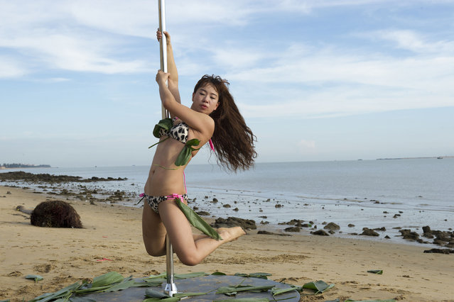 A pole dancer dressed in a bikini made up of rice dumpling leaves performs on a beach to celebrate the Dragon Boat Festival, or Duanwu Festival, in Haikou city, south China's Hainan province on June 19, 2015. Three pole dancers dressed in bikinis made up of rice dumpling leaves performed on a beach to celebrate Dragon Boat Festival or Duanwu Festival in Haikou city, south China's Hainan province, on Friday (19 June 2015). (Photo by Imaginechina/Splash News)
