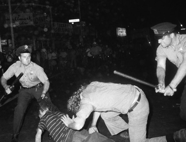 A policeman grabs a youth by the hair as another New York policeman clubs a long haired young man in a disorder in Greenwich Village, August 31, 1970 in New York. The confrontation between police and demonstrators occurred after a Gay Power march. Police chased the crowds with raised night sticks and clubbed several persons. (Photo by AP Photo)