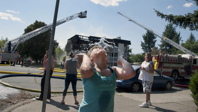 Jalesa Keen, 8, splashes herself with water from a fire hydrant as the Spokane Fire Department battles a three-alarm apartment fire Thursday, July 2,2015, in Spokane, Wash. From Seattle to Salt Lake City, the West is baking under record heat. Temperatures reaching the triple digits have made fire conditions extreme and sent folks looking for relief heading into the Fourth of July weekend. (Photo by Dan Pelle/The Spokesman-Review via AP Photo)