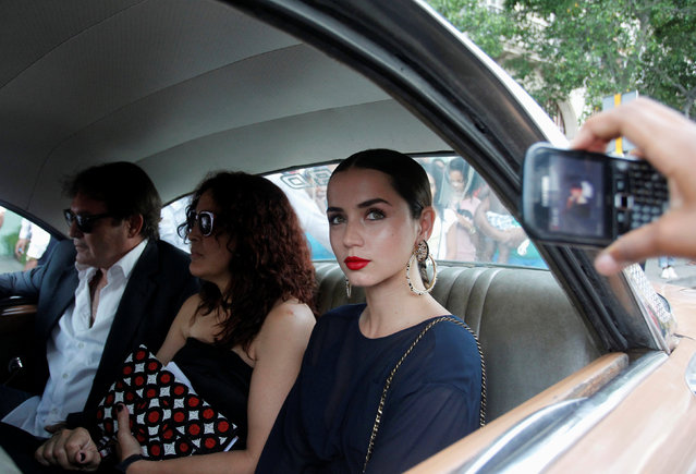 Actress Ana de Armas (R) rides in a vintage car along with others to attend a fashion show by Chanel, the first major fashion house to send models down the catwalk in Cuba, in Havana, May 3, 2016. (Photo by Reuters/Stringer)