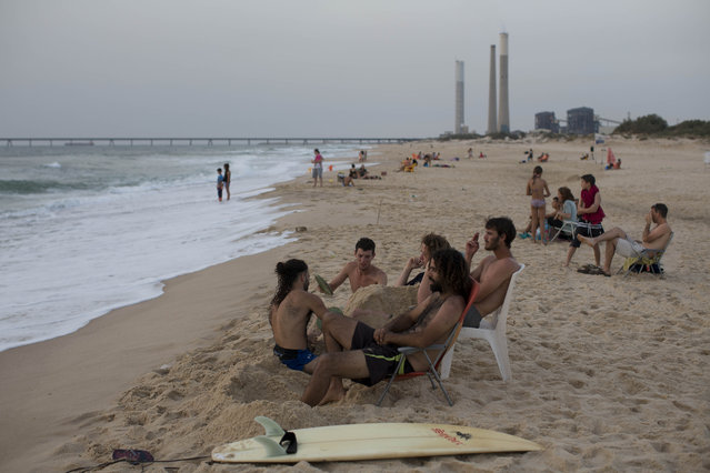 In this Saturday, June 27, 2015, photo, Israeli beach goers enjoy the day on the beach next to kibbutz Zikim, on the Israel-Gaza border. (Photo by Oded Balilty/AP Photo)