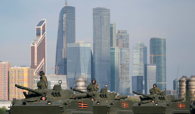"""Russian servicemen sit atop of Russian BMP-3 armoured personnel carriers before a rehearsal for the Victory Day parade, with the Moscow International Business Center also known as """"Moskva-City"""" seen in the background, at a range in Moscow, Russia, May 5, 2016. (Photo by Maxim Shemetov/Reuters)"""
