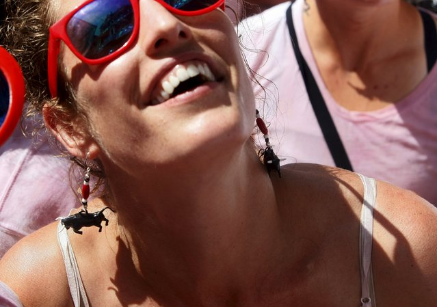 A reveller wearing earrings in the form of a bull smiles during the start of the San Fermin festival in Pamplona July 6, 2015. (Photo by Reuters/Stringer)