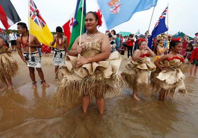 Pacific island women and girls stand in the water in Newcastle Harbour as they watch a flotilla of water craft block shipping access to Australia's largest coal port in Newcastle, north of Sydney, Australia, May 8, 2016. (Photo by Jason Reed/Reuters)