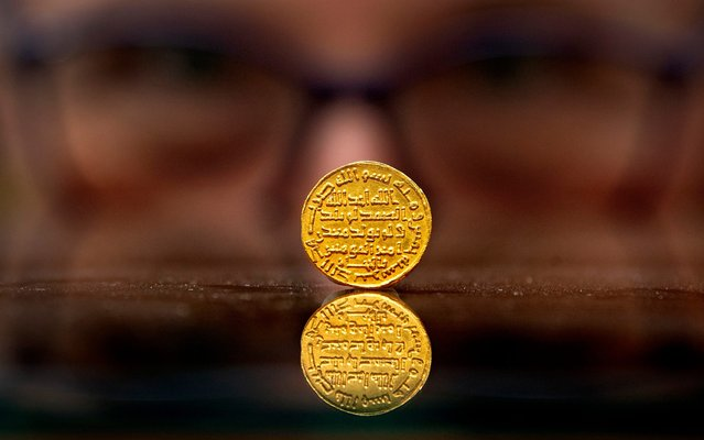 A member of staff at Morton & Eden holds an extremely rare early Islamic gold coin on Thursday September 12, 2019, which is expected to fetch £1.4m at auction in London. Measuring a 20mm across, about the size of a modern £1 piece, it is one of the world's rarest and most treasured Islamic gold coins from the first dynasty of Islam, the Umayyad gold dinar dated 105h (723AD). (Photo by Victoria Jones/PA Images via Getty Images)