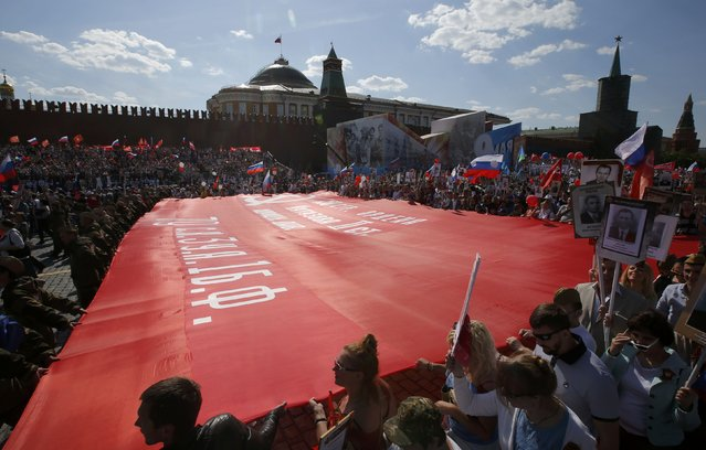 People carry a banner, a replica of the so-called Victory Standard which was erected at the top of the Reichstag building in Berlin at the end of World War Two, as they take part in the Immortal Regiment march during the Victory Day celebrations at Red Square in Moscow, Russia, May 9, 2016. (Photo by Sergei Karpukhin/Reuters)