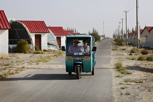 In this September 21, 2018, photo, Han Chinese ride in a tricycle passing by farmhouses at the Unity New Village in Hotan, in western China's Xinjiang region. The Trump administration, locked in a trade war with China, is increasing the pressure on Beijing over what it says is the systematic oppression of ethnic minority Muslims. American officials hosted a panel Tuesday, Sept. 24, 2019, on the sidelines of the United Nations General Assembly gathering in New York to highlight the plight of Uighurs, whose native land in China's far western Xinjiang province they say is a police state. (Photo by Andy Wong/AP Photo)