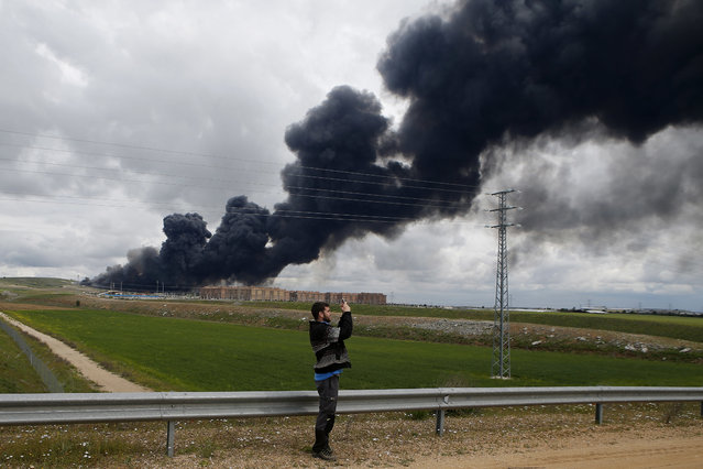 A man takes photos with a cell phone of billowing black smoke rising behind large housing blocks from a huge fire in Sesena, central Spain, Friday, May 13, 2016. (Photo by Paul White/AP Photo)