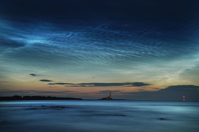 Rare noctilucent clouds shine brightly across Whitley Bay beach over St Mary's Lighthouse at Whitley Bay, England on June 17, 2019. Noctilucent clouds are made of ice crystals and are only visible during astronomical twilight. (Photo by Owen Humphreys/PA Wire Press Association)