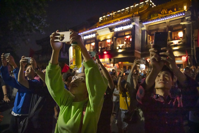 People use their smartphones to take photos at Qianhai Lake of fireworks in the distance at Tiananmen Square as part of a gala evening commemorating the 70th anniversary of the founding of Communist China in Beijing, Tuesday, October 1, 2019. (Photo by Mark Schiefelbein/AP Photo)