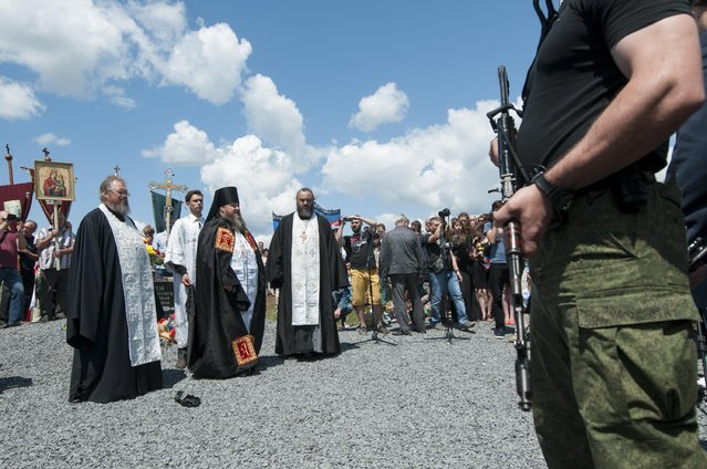 Orthodox priests attend a memorial ceremony at the crash site of the Malaysian Airlines MH17 plane near the village of Hrabove, eastern Ukraine, Friday, July 17, 2015. (Photo by Antoine E. R. Delaunay/AP Photo)