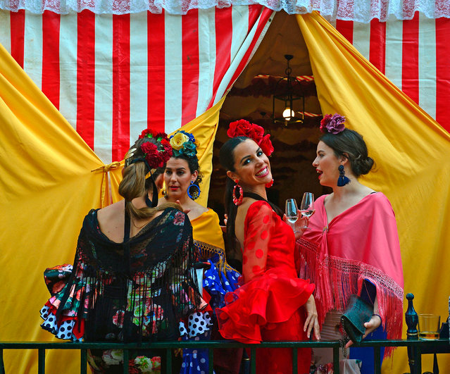 """A woman wearing a traditional Sevillian dress smiles as she drinks """"Fino"""" wine with friends during the """"Feria de Abril"""" (April Fair) in Sevilla on April 30, 2017. (Photo by Cristina Quicler/AFP Photo)"""