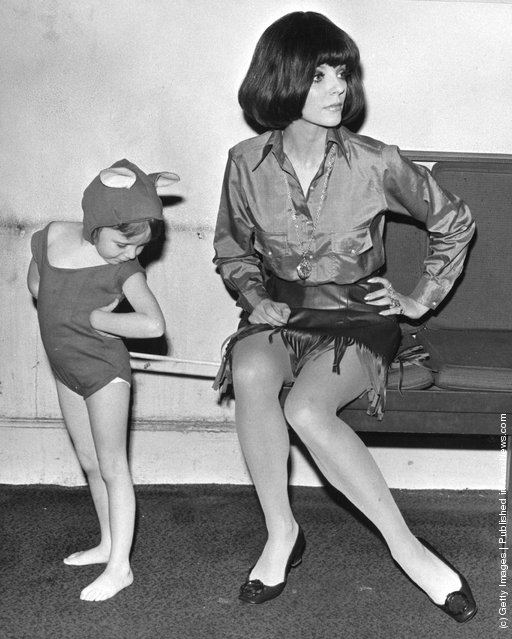 1968: Actress Joan Collins unwittingly sits on the 'tail' of her five-year old daughter Tara's mouse suit during rehearsals for 'Airs and Graces' the childrens matinee in aid of the Forces Help Society and Lord Roberts Workshops, at the Scala Theatre