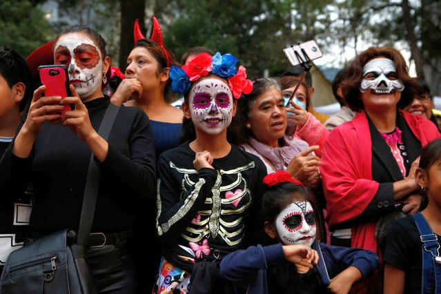 People attend the Catrinas parade down Mexico City's iconic Reforma avenue during celebrations for the Day of the Dead in Mexico, Saturday, October 26, 2019. (Photo by Ginnette Riquelme/AP Photo)