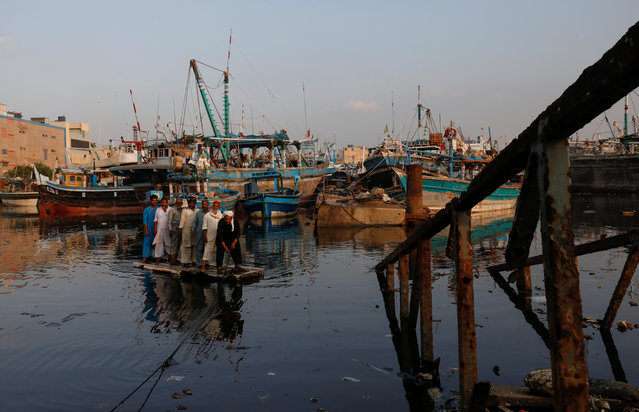 Fishermen sail on an improvised raft with anchored fishing boats in the background as they are crossing next to a submerged pedestal bridge (R) at Fish Harbor in Karachi, Pakistan on October 7, 2019. (Photo by Akhtar Soomro/Reuters)