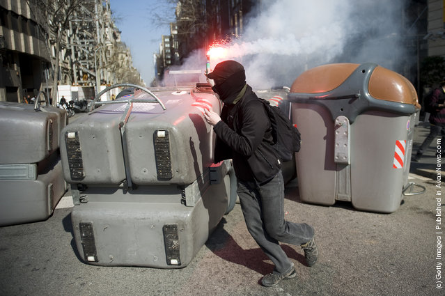 A student sets fire to garbage containers with a flare during a demonstration on February 29, 2012 in Barcelona