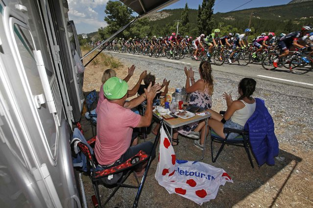 Cycling supporters applaud riders as they cycle during the 161-km (100 miles) 17th stage of the 102nd Tour de France cycling race from Digne-les-Bains to Pra Loup in the French Alps mountains, France, July 22, 2015. (Photo by Eric Gaillard/Reuters)