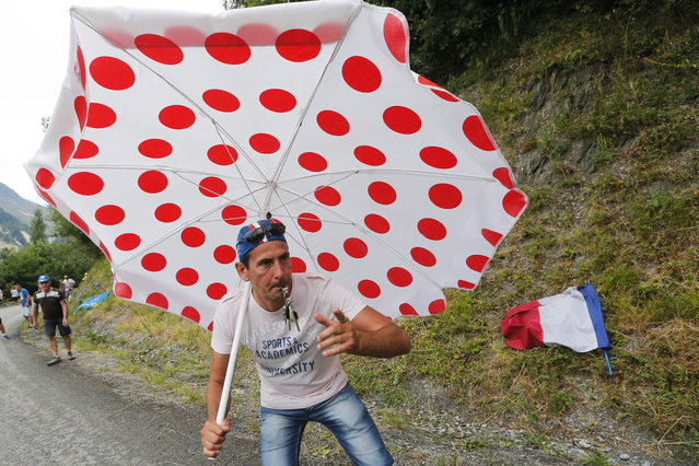 A spectator with an umbrella in the colors of the best climber's dotted jersey waits for the riders during the nineteenth stage of the Tour de France cycling race over 138 kilometers (85.7 miles) with start in Saint-Jean-de-Maurienne and finish in La Toussuire, France, Friday, July 24, 2015. (Photo by Christophe Ena/AP Photo)