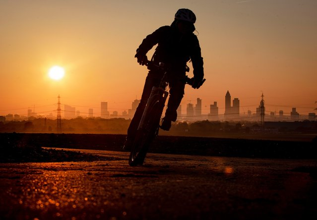 A woman rides her bike to work in the outskirts of Frankfurt, Germany, early Wednesday, October 30, 2019. (Photo by Michael Probst/AP Photo)