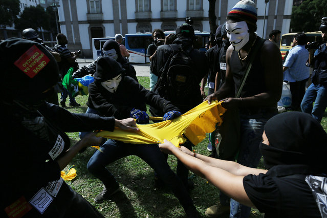 Masked anti-World Cup protesters rip apart a Brazilian national team soccer jersey during a demonstration, in downtown Rio de Janeiro, Brazil, Thursday, June 12, 2014, hours before the first World Cup match was to be played in Sao Paulo. (Photo by Leo Correa/AP Photo)