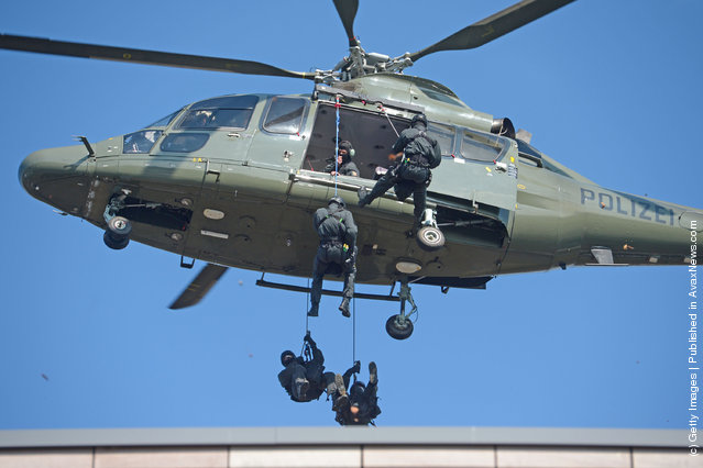 Members of Germany's elite police unit, the Spezialeinsatzkommando, or SEK, demonstrate an abseil deployment from a helicopter during a media event